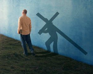 A man carries his Bible while his shadow carries the cross