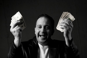 A man celebrating holding handfuls of green American cash with selective color. Shallow depth of field with focus on the face.