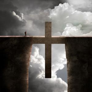 A man crosses over the bridge shaped as a cross