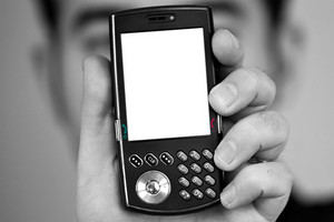 A man holding up a cellular phone.  Clipping path included for the white space on the lcd screen.