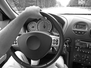 A man holds the steering wheel with one hand while driving on the highway.