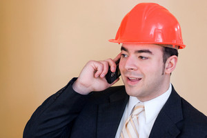 A man in a business suit and hard hat talks on his cell phone.  He could be a custom home builder or even an engineer or architect.