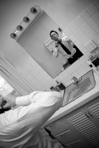 A man in a shirt and tie in the bathroom getting ready to go.  Shallow depth of field.
