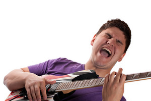 A man in his late teens playing his electric guitar over a white background.