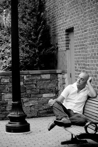 A man in his twenties sitting casually on a bench in an urban area.