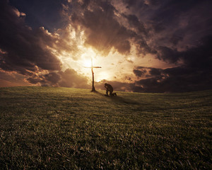 A man kneeling at a cross at sunset.