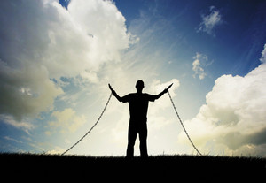 A man lifts his arms in praise even though he is in chains