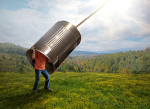 A man listens to the sounds from above with a tin can.