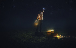 A man places the stars in the night sky