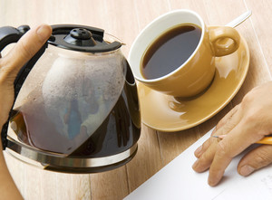 A Man Pouring Coffee Into A Cup