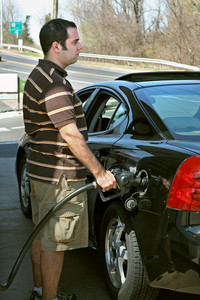 A man pumping high priced gas into his car with a disgusted look on his face.