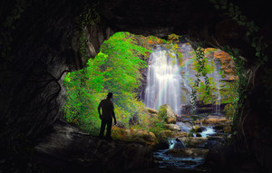 A man reaches the end of a cave and finds a waterfall