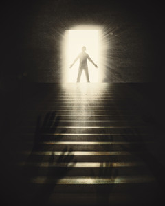 A man reaches the top of stairs and to the light