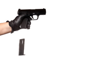 A man reloading a weapon drops the clip from a black handgun. Slight motion blur on the falling ammunition clip.