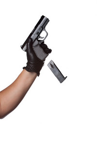A man reloading a weapon drops the clip from a black handgun.  Works great for crime or home security concepts.