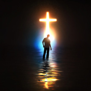 A man stands in front of a colorful glowing cross