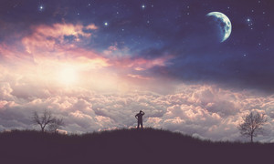 A man stands on a hill and looks out over the world