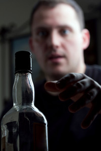 A man struggling with alcoholism reaches for his bottle of liquor. Shallow depth of field.