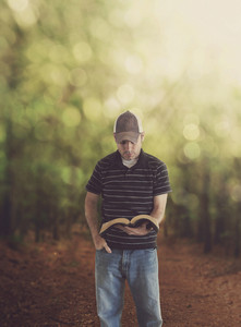 A man studies his Bible in the forest