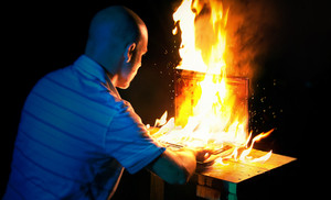 A man uses a laptop while it is engulfed in flames.