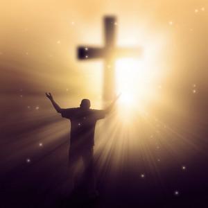A man walking towards a cross with sunbeams