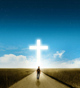 A man walking towards a large glowing Christian cross