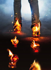 A man walks with his shoes on fire and leaves fire footprints.