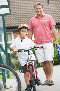 A man watching his son on a bicycle