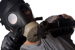 A man wearing a gas mask pointing two guns at the viewer. Shallow depth of field.  Works great for crime or warfare concepts.