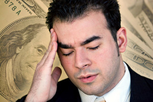 A man with a headache from all of the stress of his financial problems.