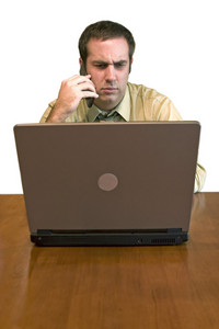 A man working from home with his cell phone and laptop. He has an upset or serious look on his face.