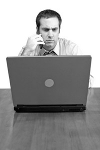 A man working from home with his cell phone and laptop in black and white. He has an upset or serious look on his face.