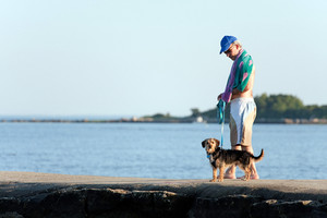 A middle aged man walks a cute borkie beagle yorkie mix puppy at the beach.