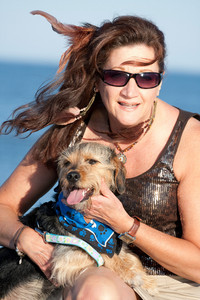 A middle aged woman by the ocean holding a cute mixed breed Beagle Yorkshire terrier dog also referred to as a Borkie.