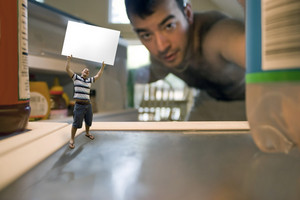 A miniature man holding up a blank sign inside the refrigerator.  Possible text on the sign could be WHATS FOR DINNER or WE NEED FOOD.  Use your imagination!  Shallow depth of field.