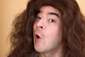 A model with really long hair has a funny expression on his face.