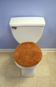 A modern looking toilet with a fuzzy, orange toilet seat cover.
