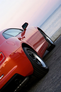 A modern sports car parked at the beach around sunset.