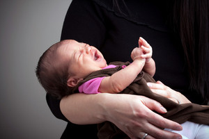 A mom holds a young newborn baby girl in her arms that is upset and crying.