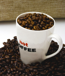 A Mug Of Hot Coffee With Coffee Beans