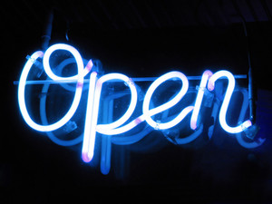 "A neon ""open"" sign glowing blue in the window of a restaurant."