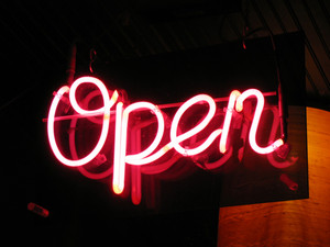 "A neon ""open"" sign glowing red in the window of a restaurant."