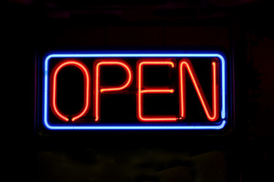 A neon OPEN sign glowing red in the window of a restaurant.