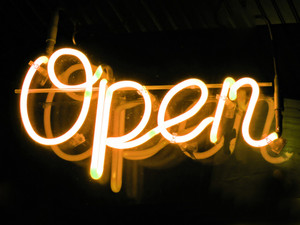 A neon orange OPEN sign glowing in the window of a restaurant.
