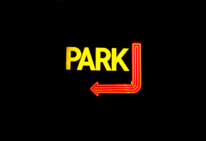 A neon parking sign isolated over black.