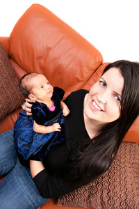 A newborn baby being held in the arms of her mother while seated on the sofa.