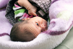 A newborn baby girl waking up in her crib on fuzzy pink blankets. Shallow depth of field.