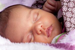 A newborn baby sleeping peacefully under blankets.