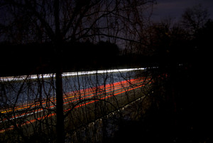 A nighttime highway shot using slow shutterspeed - glowing light trails are visible through the trees.