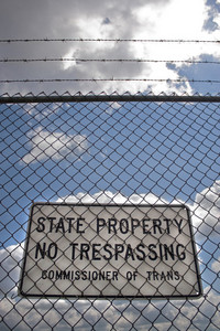 A no trespassing sign that reads STATE PROPERTY NO TRESPASSING outside an airport.